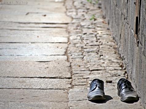 Buty porzucone na chodniku.