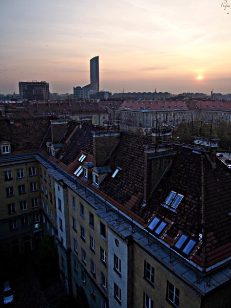 Zachód słońca nad dachami kamienic. Po lewej Arkady Wrocławskie i Sky Tower.