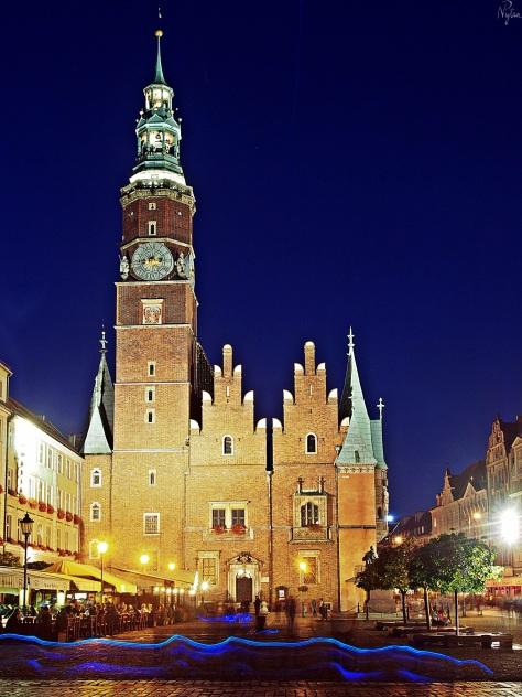 Widok wieczorem na rynek i ratusz we Wrocławiu od strony pierzei zachodniej, na ujęciu o długiej ekspozycji. Niebieskie maziaje na dole to efekt spowodowany przez przechadzających się sprzedawców świecących i latających zabawek do rzucania. ;)